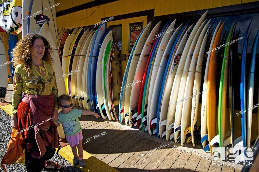 Stock Photo: Shops surfers in Haleiwa. O'ahu. Hawaii. Mother and daughter in front of a surfer shop. Historic Surf n Sea shop (1921), Haleiwa, Oahu, Hawaii, USA.