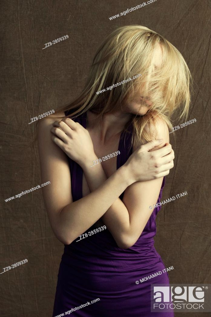 Stock Photo: Slim young blond woman hair covering face.