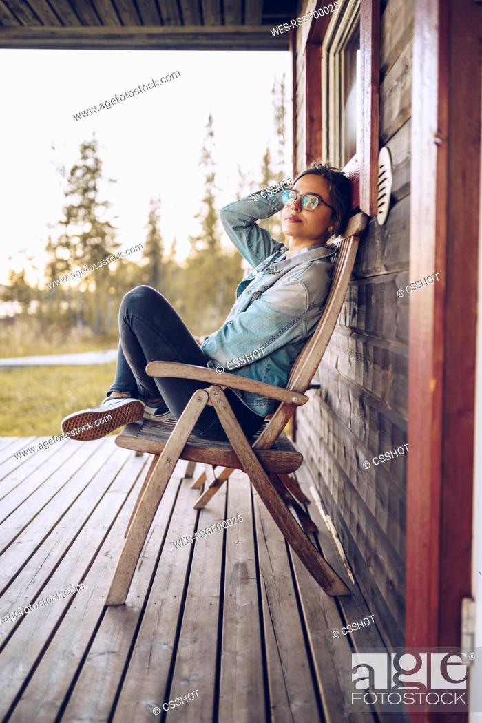 Imagen: Sweden, Lapland, portrait of young woman sitting on chair on veranda relaxing.