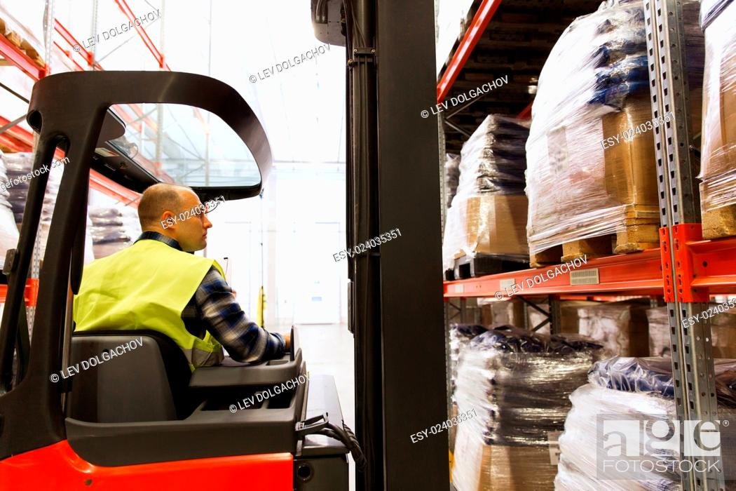 Stock Photo: wholesale, logistic, loading, shipment and people concept - man or loader operating forklift loader at warehouse.