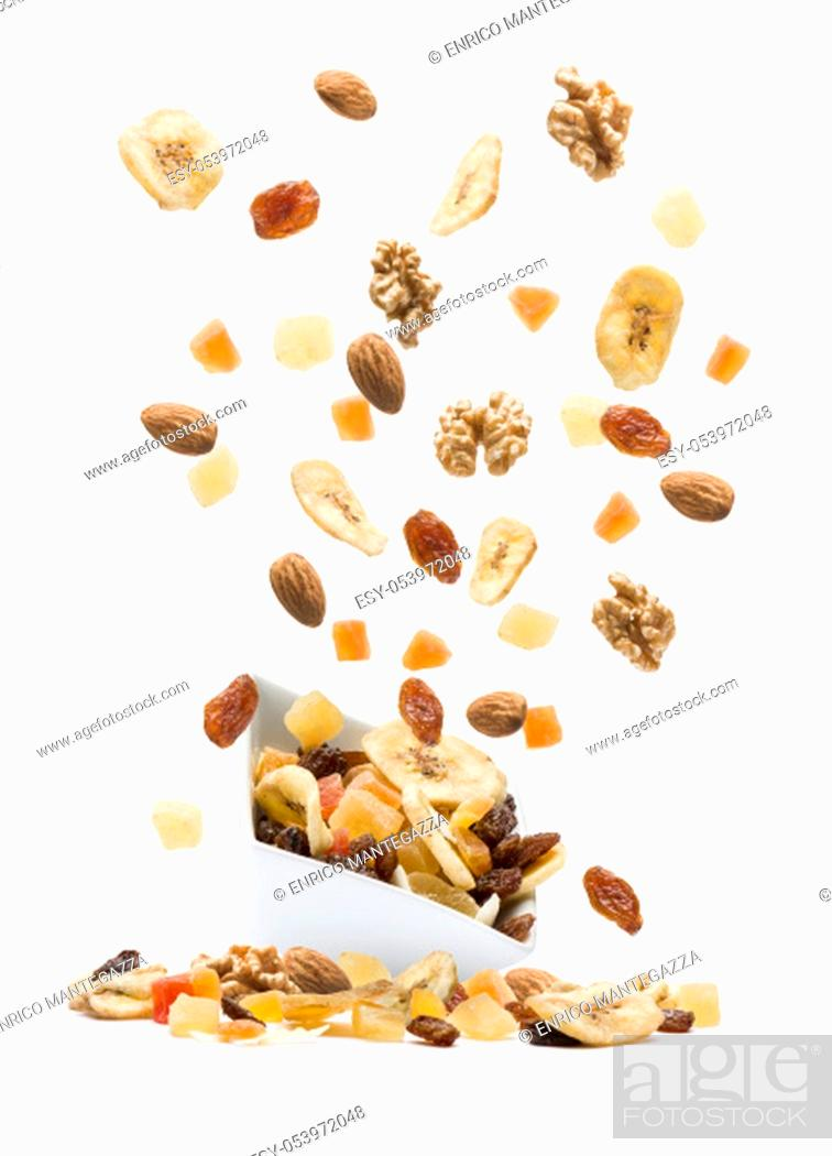 Stock Photo: Dried fruits jumping out white bowl on white background.