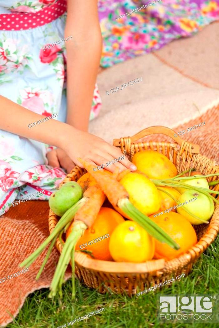 Stock Photo: girl sitting on grass and taking carrot out of basket.
