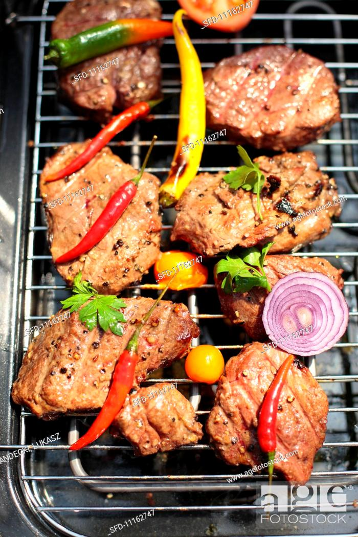Stock Photo: Beef with chili peppers and sliced onions on the electric grill.