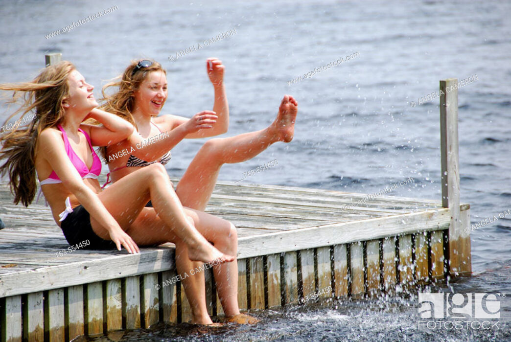 Stock Photo: sisters 13 and 18 kicking up water while sitting on dock at lake.