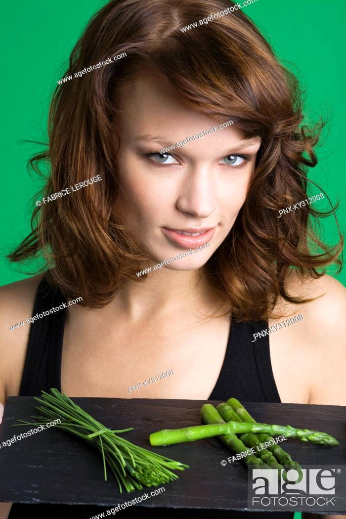 Stock Photo: Young woman holding tray of asparagus and chives.