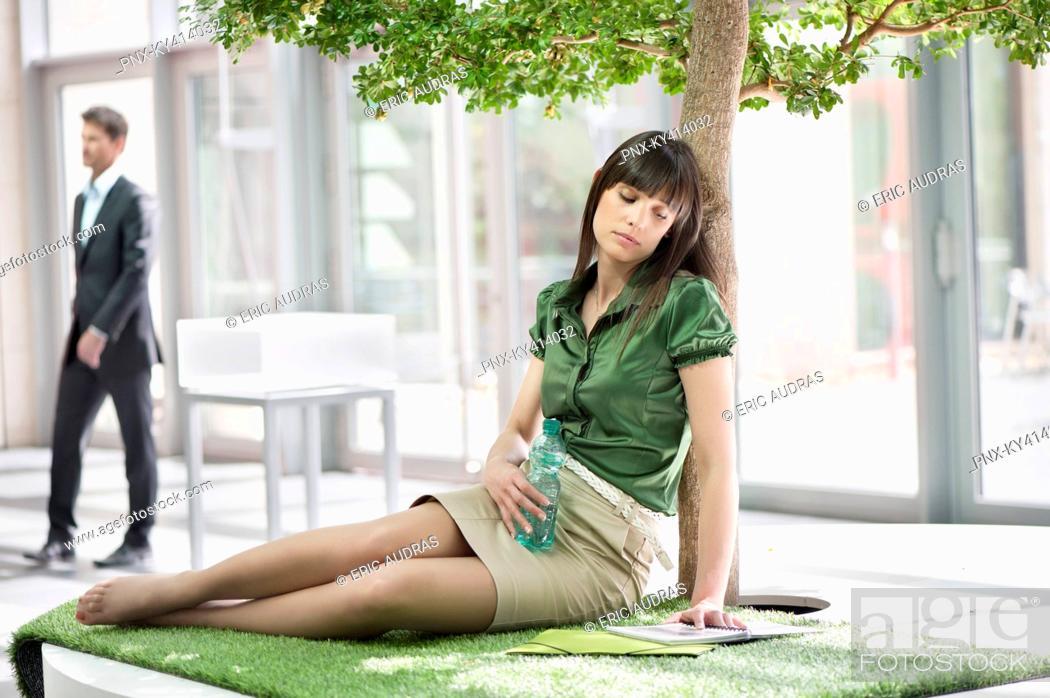 Stock Photo: Businesswoman relaxing on grass mat.