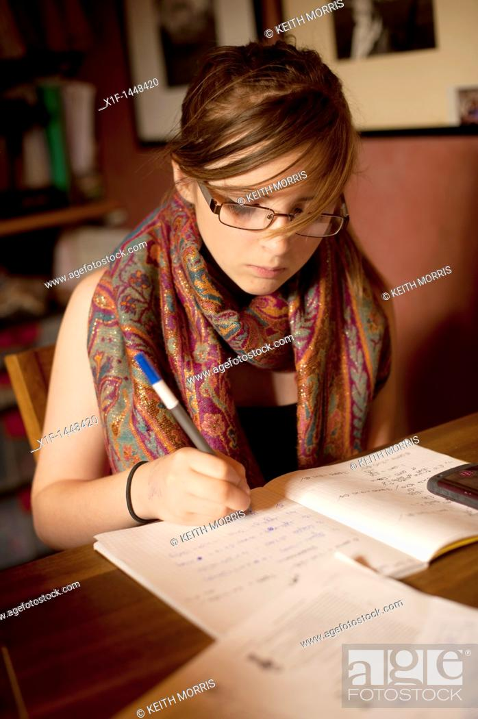 Stock Photo: A 12 13 year old girl doing her mathematics homework at home UK.