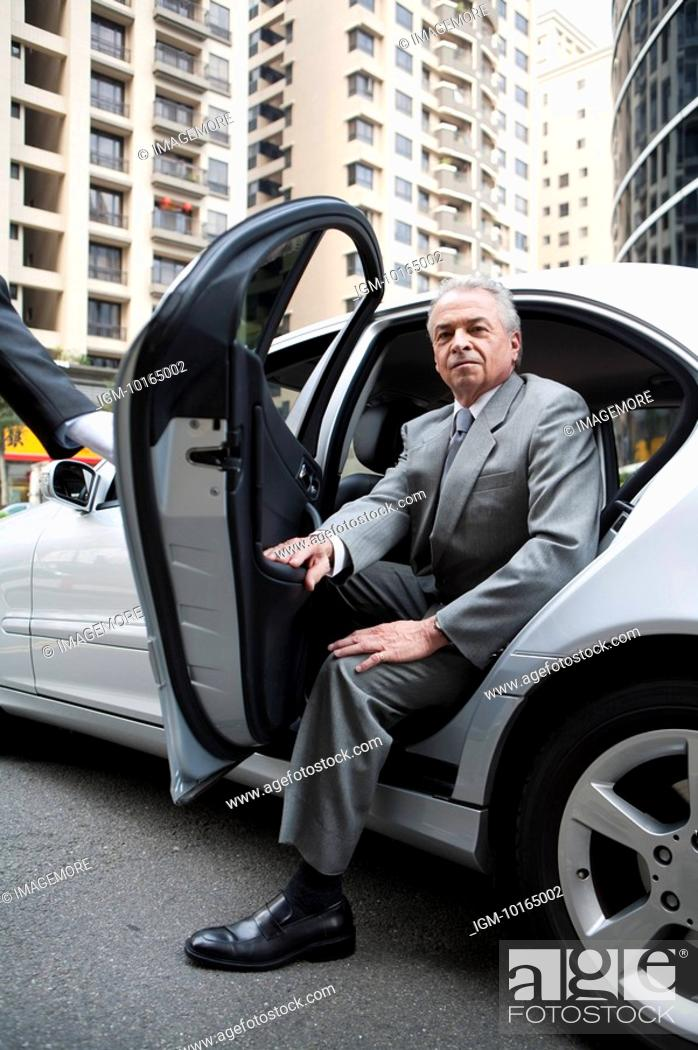 Stock Photo: Senior businessman getting off the car and looking at the camera.
