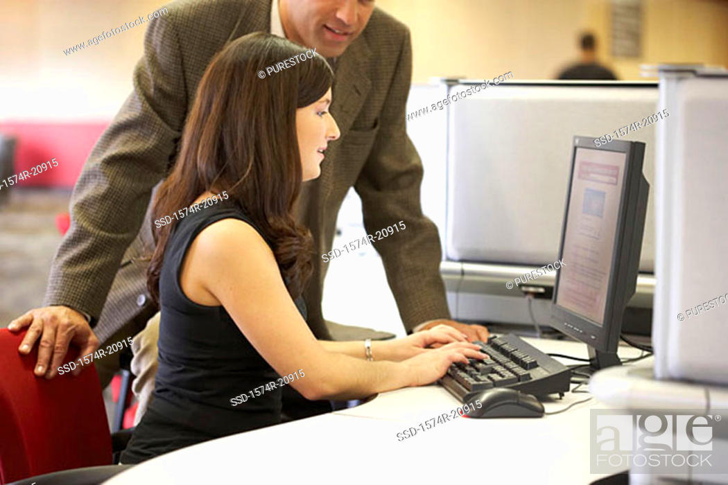 Stock Photo: Side profile of a college student working on a computer with her professor standing beside her.