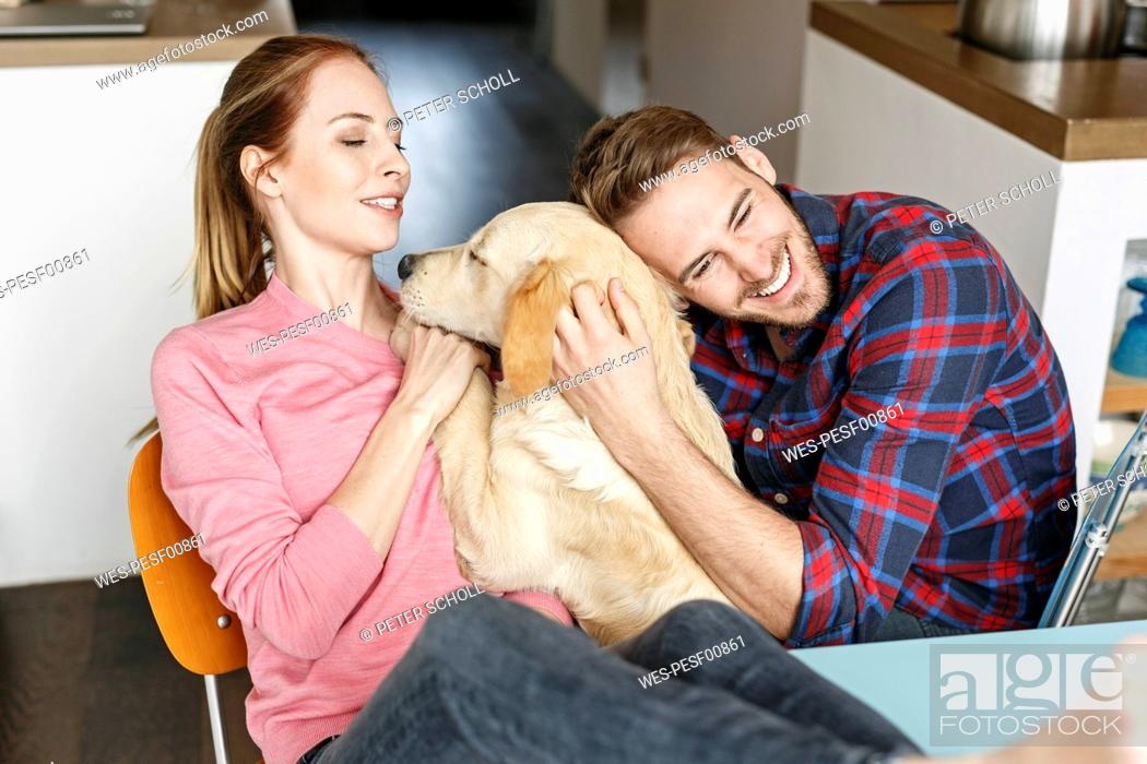 Stock Photo: Happy young couple cuddling with dog at home.