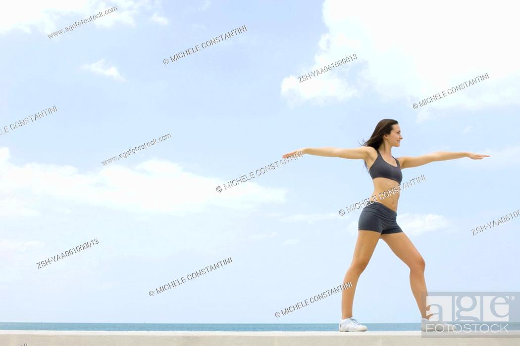 Stock Photo: Young woman in sports clothing standing with arms outstretched, low angle, side view.