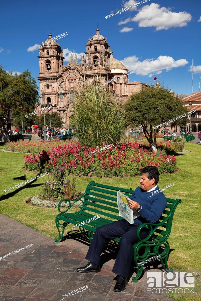 Stock Photo: Peruvian man reading a newspaper at the park in the main square with the Cathedral at the background, Cusco, Peru, South America.