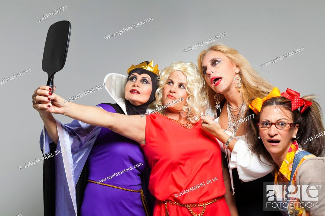 Stock Photo: Women with costumes looking at mirror.