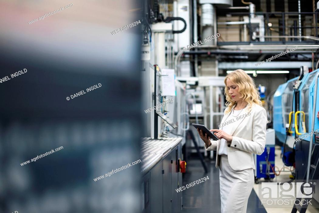 Stock Photo: Woman using tablet at machine in factory shop floor.