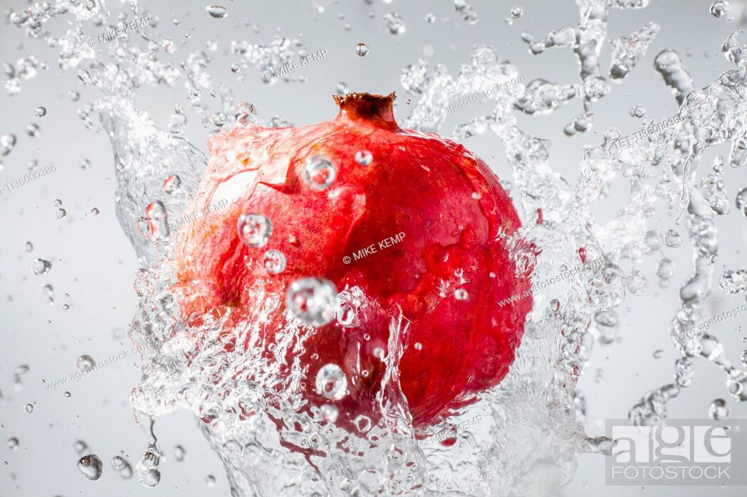 Stock Photo: Droplets splashing on pomegranate.
