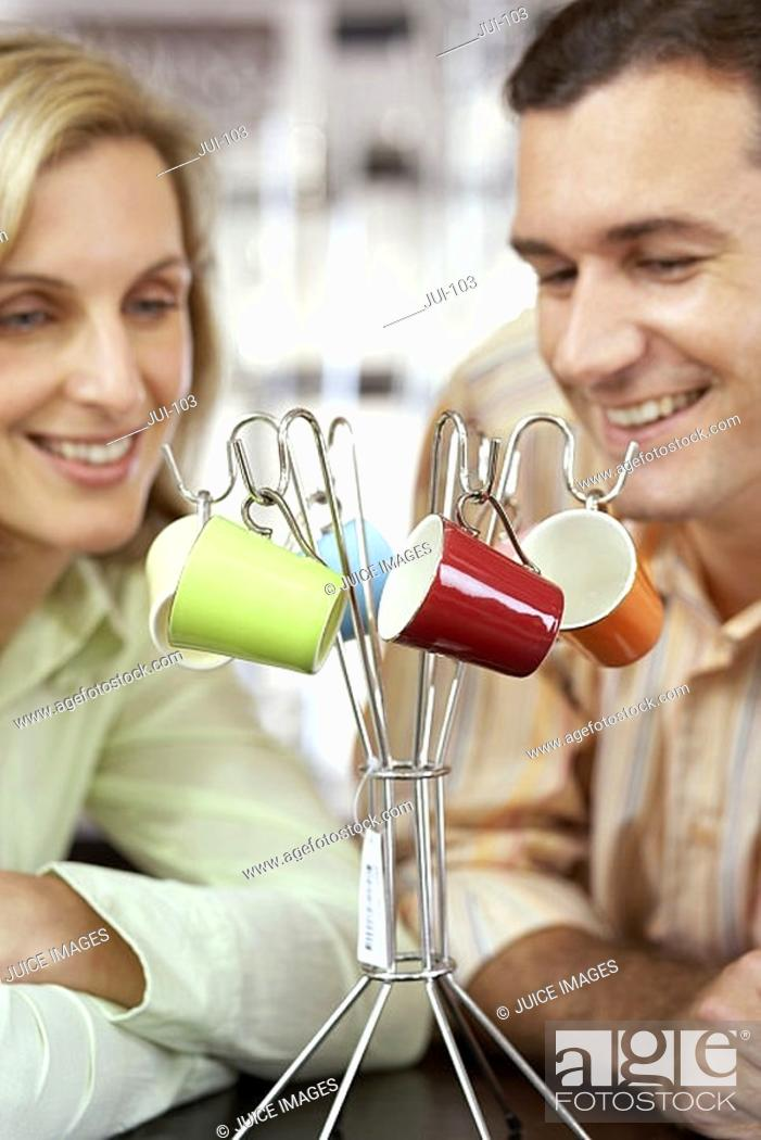 Stock Photo: Couple looking at multi-coloured expresso cups hanging on rack in shop, close-up.