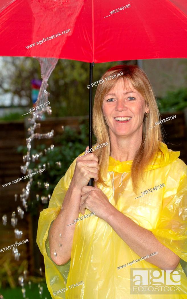 Stock Photo: Woman wearing a yellow poncho holding a red umbrella in the rain,.