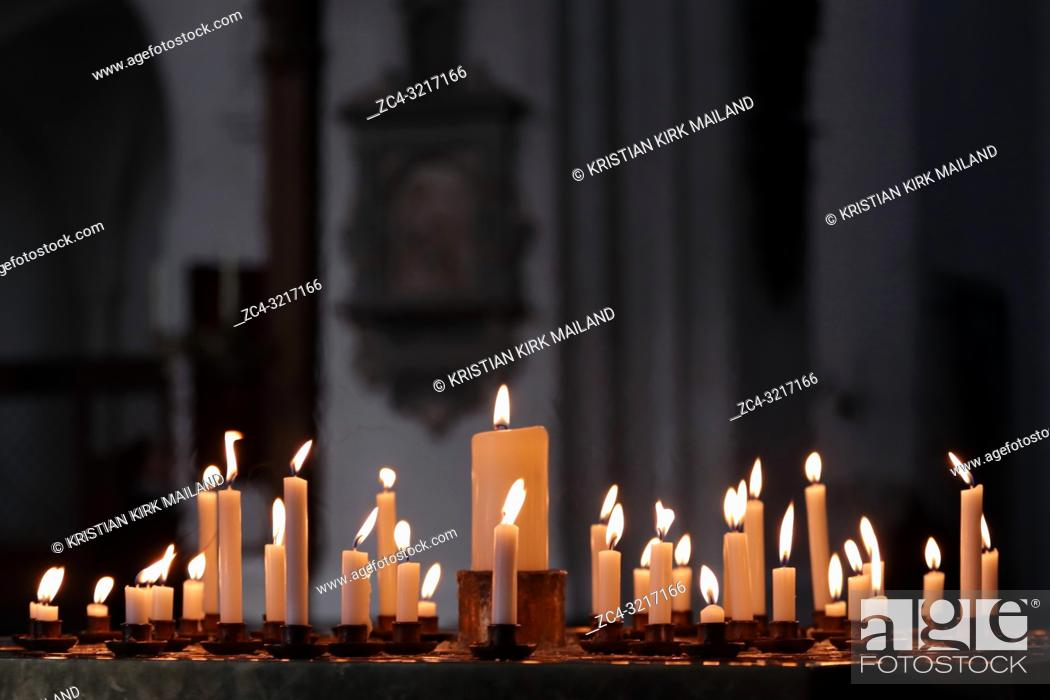 Stock Photo: Candles lit by worshippers in a Christian church.