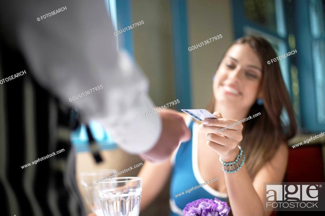 Stock Photo: Woman giving credit card to waiter (close-up).