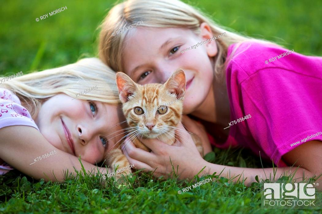 Stock Photo: sisters with kitten.