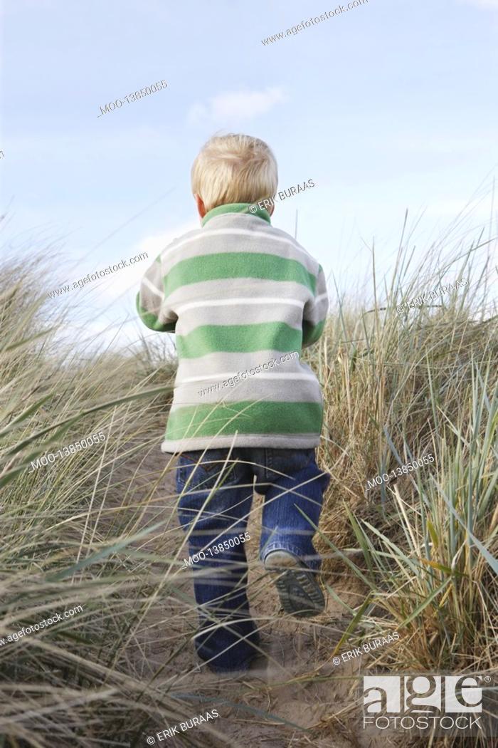 Stock Photo: Boy 3-4 walking on path among long grass.