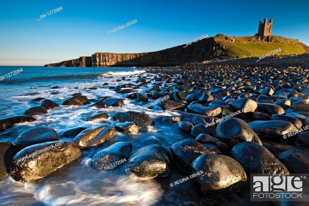 Stock Photo: Dunstanburgh Castle, with basalt boulders on beach, autumn, Northumberland, England.