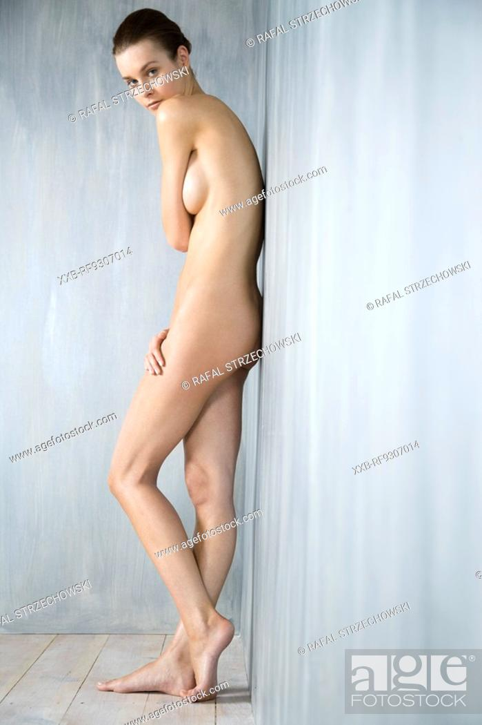 Stock Photo: beauty woman standing next to wall.