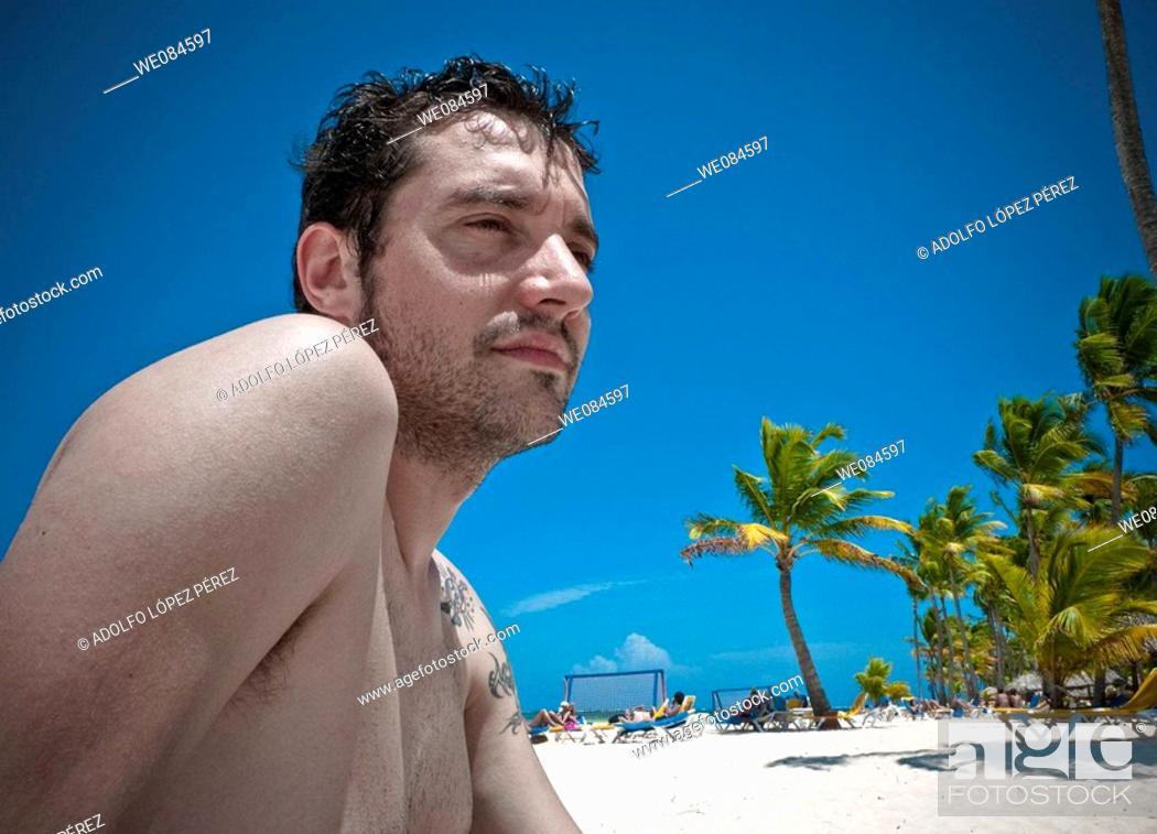 Stock Photo: chico sentado en la playa de Punta Cana, República Dominicana.