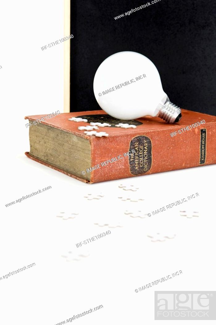 Stock Photo: bulb and dictionary in front of blackboard.