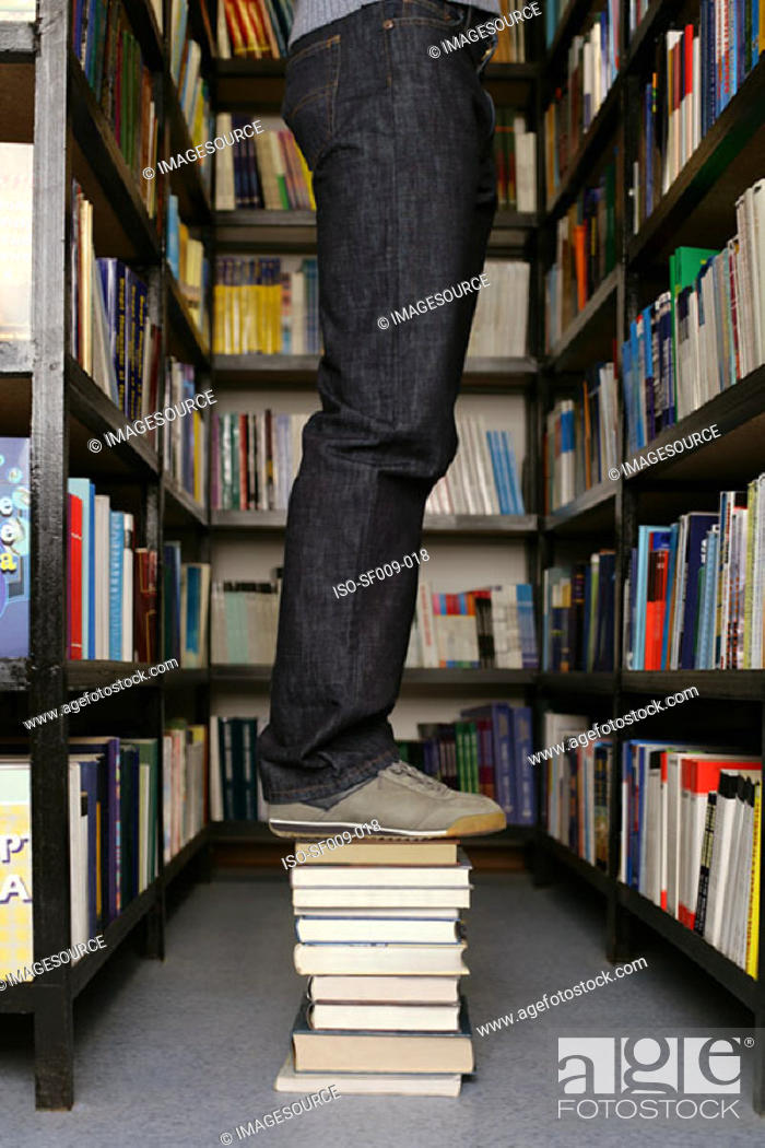 Stock Photo: Young person standing on books in library.