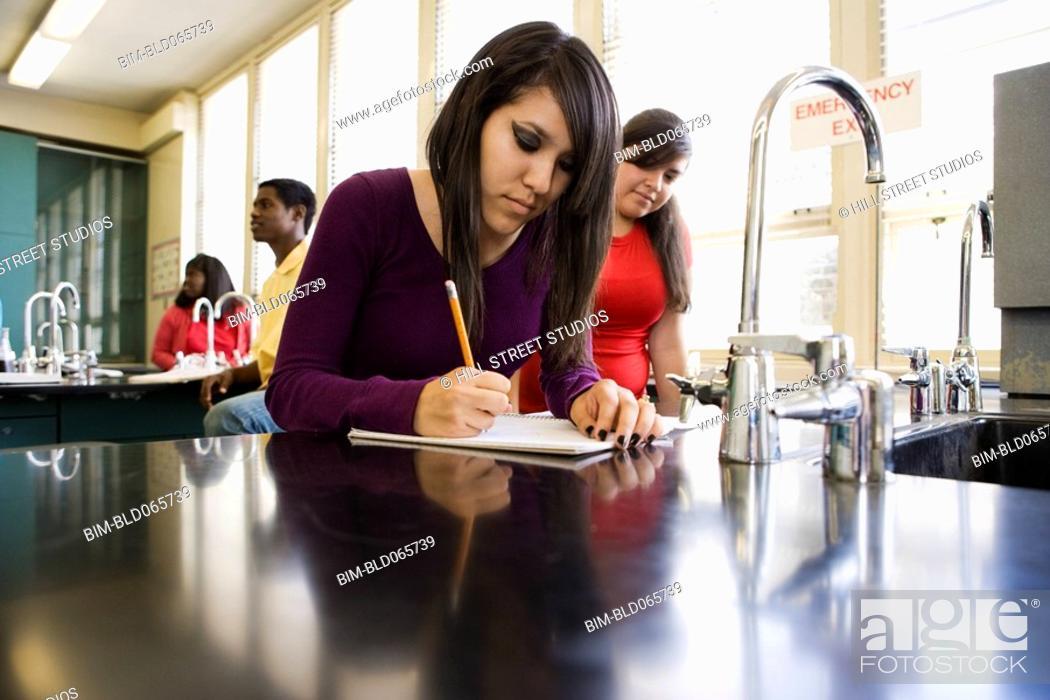 Stock Photo: Hispanic teenage girl studying in chemistry lab.