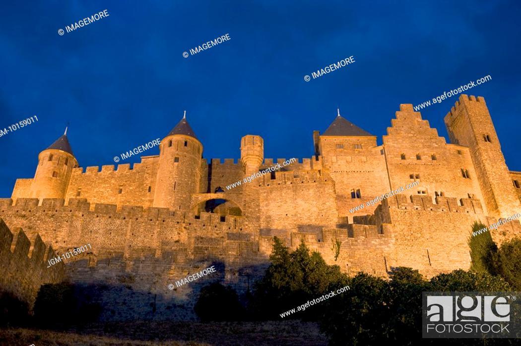 Stock Photo: France, Languedoc, Carcassonne, Castle walls illuminated at night.