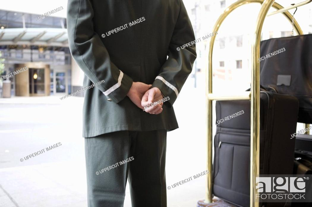 Stock Photo: Bellhop with hands behind back.