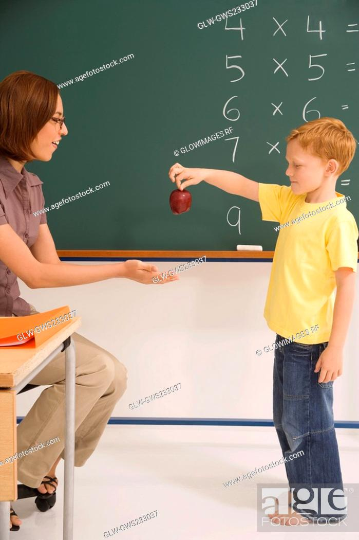 Stock Photo: Side profile of a schoolboy giving an apple to his female teacher in a classroom.