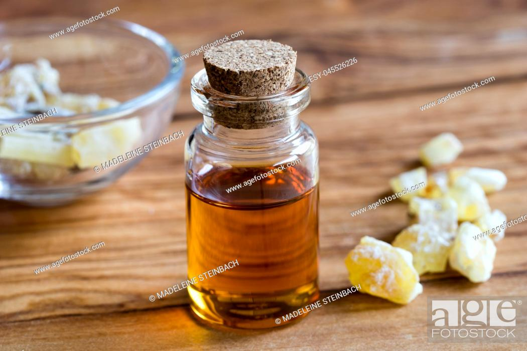 Stock Photo: A bottle of frankincense essential oil with frankincense resin crystals in the background, on a wooden table.