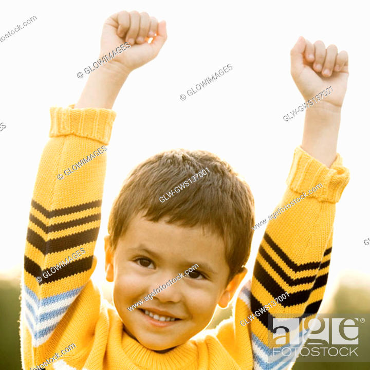 Stock Photo: Close-up of a boy standing with his hands raised.