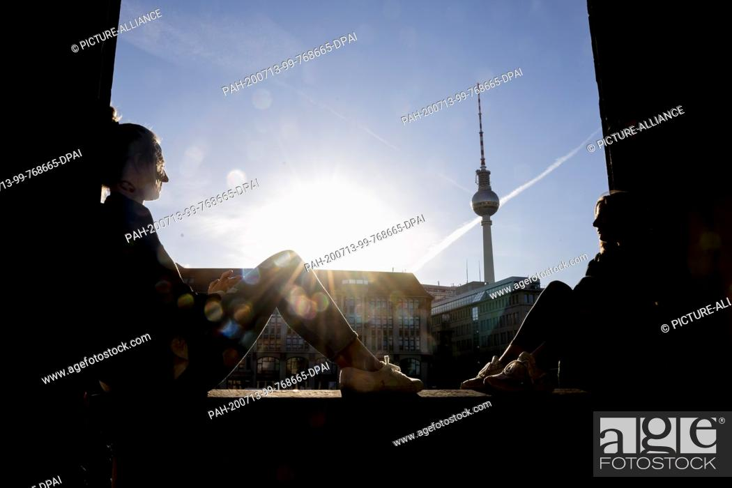 Stock Photo: 13 July 2020, Berlin: Two women are sitting in the morning sun in front of the Berlin television tower on Museum Island. Photo: Christoph Soeder/dpa.