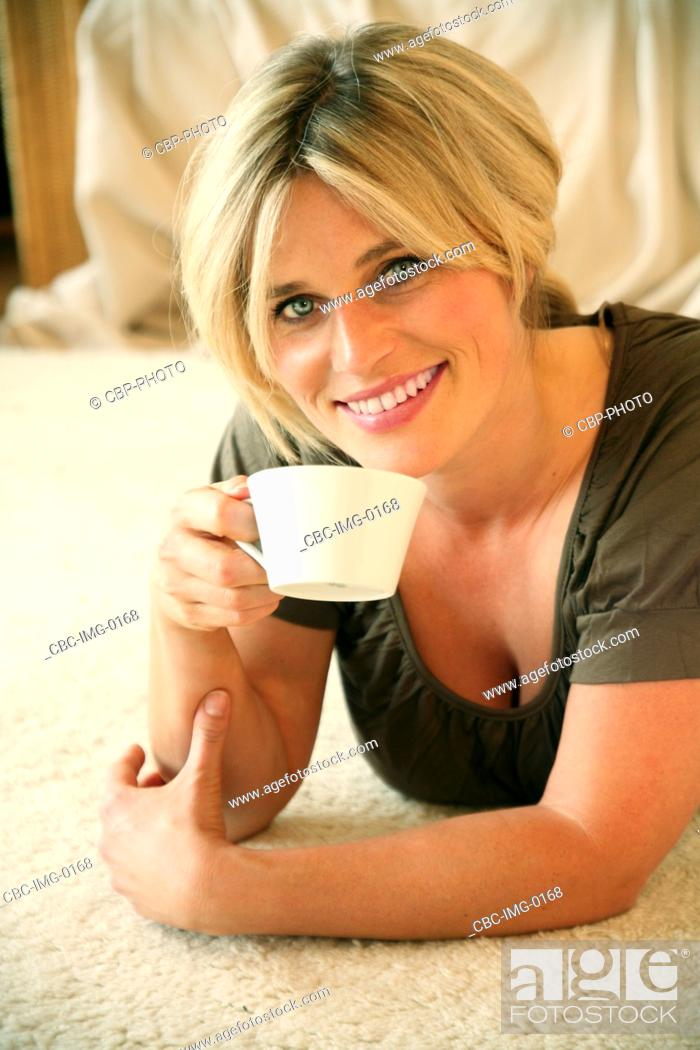 Imagen: Portrait of Young Woman Having a Cup of Coffee, Lying on Floor.