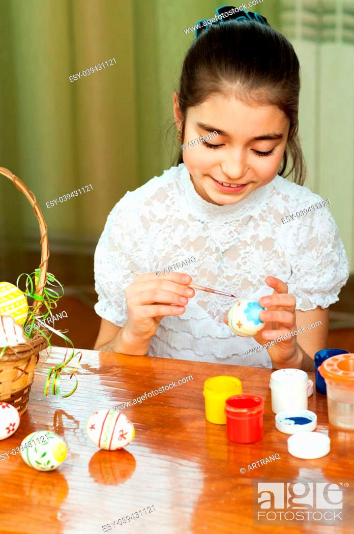 Stock Photo: beautiful girl colored Easter eggs sitting at the table.