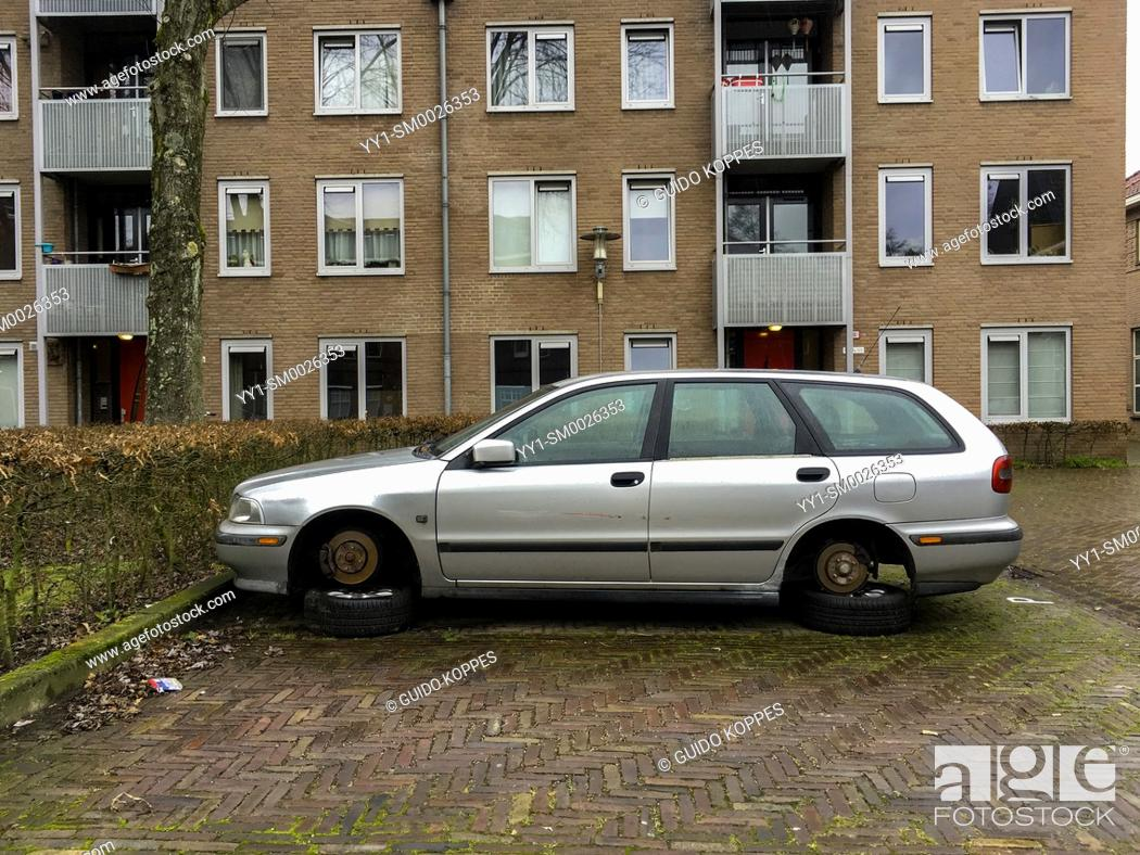 Stock Photo: Tilburg, Netherlands. Elder Volvo in Need of Repairs and with his wheels disattached stashed for long term period on a residential parking lot.