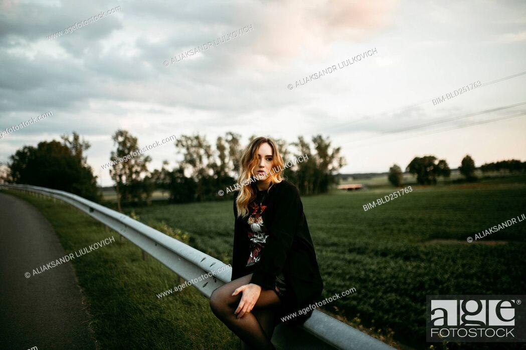 Stock Photo: Caucasian woman sitting on guardrail near road.