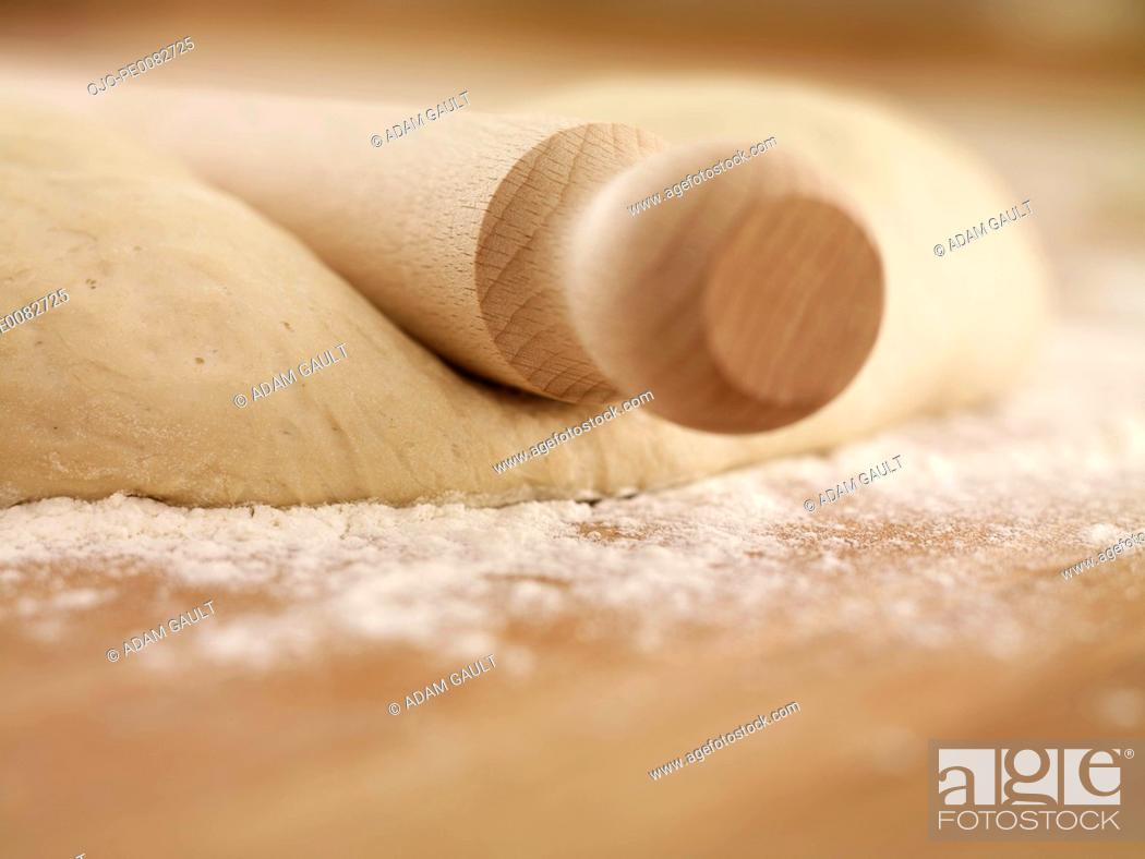 Stock Photo: Close up of rolling pin on dough.
