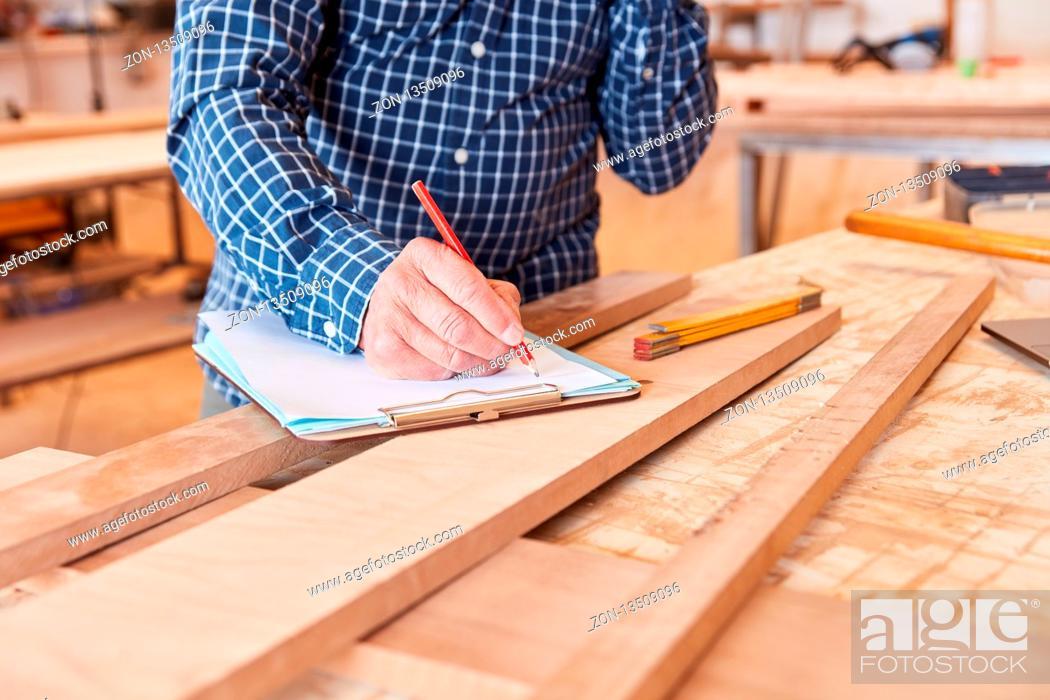 Imagen: Handwerker mit Bleistift und Checkliste plant und organisiert einen Auftrag.