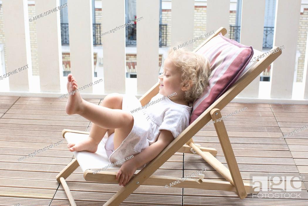 Stock Photo: Little girl sitting on deckchair.