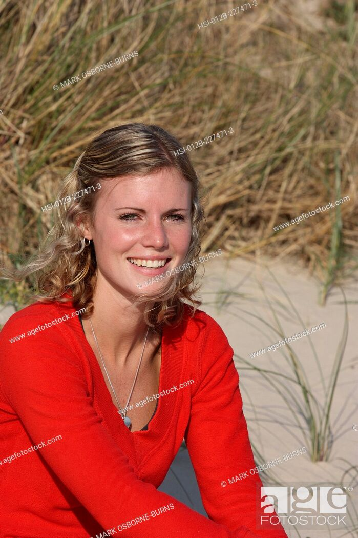 Stock Photo: Portrait of a young blonde woman outdoors by sand dune at the beach.