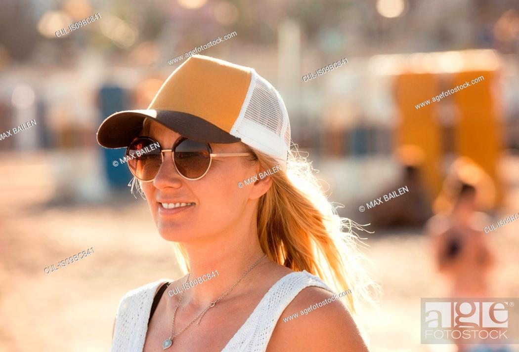 Stock Photo: Portrait of woman on beach, wearing sunglasses and cap, Sitges, Catalonia, Spain.