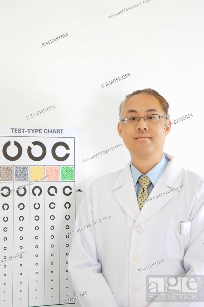 Stock Photo: Doctor standing before eye chart and looking at the camera.