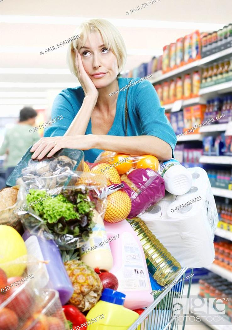 Stock Photo: Woman with shopping trolley full of groceries.