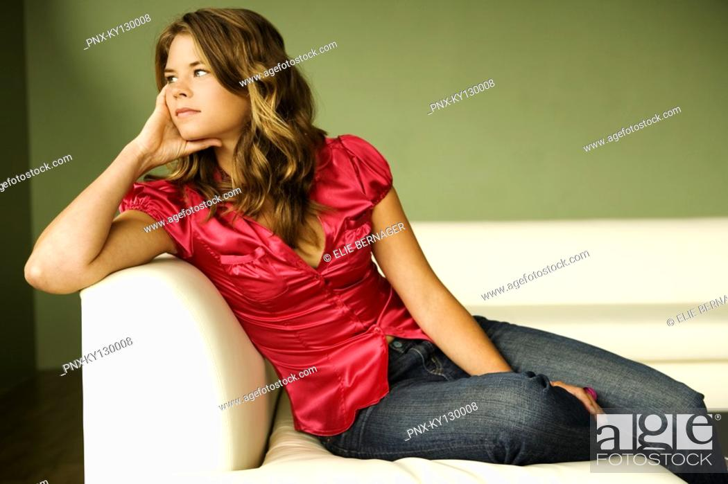 Stock Photo: Young thinking woman sitting on a sofa.