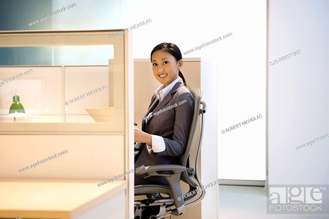Stock Photo: Smiling businesswoman working in office cubicle.